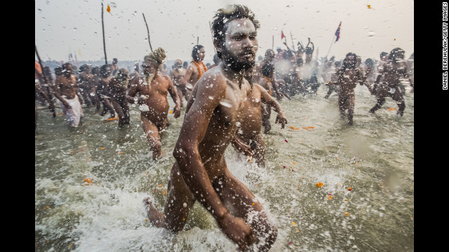 Naga Sadhus run into the waters of the Ganges River during the bathing day of the Maha Kumbh Mela on January 14.