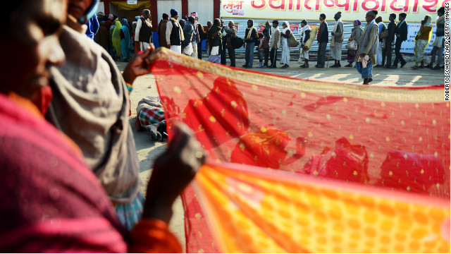 Devotees line up to receive a free meal near women drying saris on February 8.