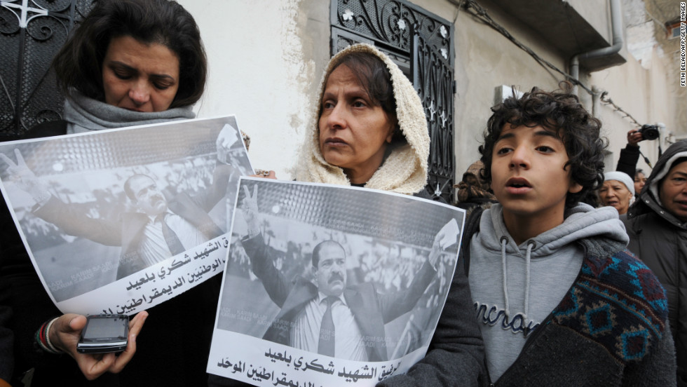 Tunisian women hold placards featuring late opposition leader Chokri Belaid.