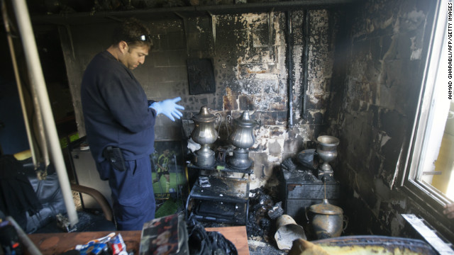 A club official examines the charred remains of the trophies won by Israeli league side Beitar Jerusalem after an arson attack on its clubhouse.