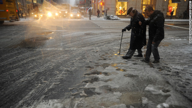 New York City residents cross a street covered in slush on Friday during a storm affecting the Northeast on Friday. 