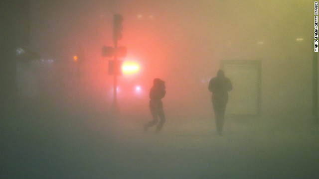 People walk through the blowing snow while a blizzard arrives in the Back Bay neighborhood on February 8 in Boston.