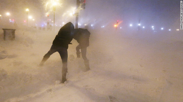Pedestrians shield themselves from blowing snow as a blizzard arrives in the Back Bay neighborhood of Boston on Friday, February 8.