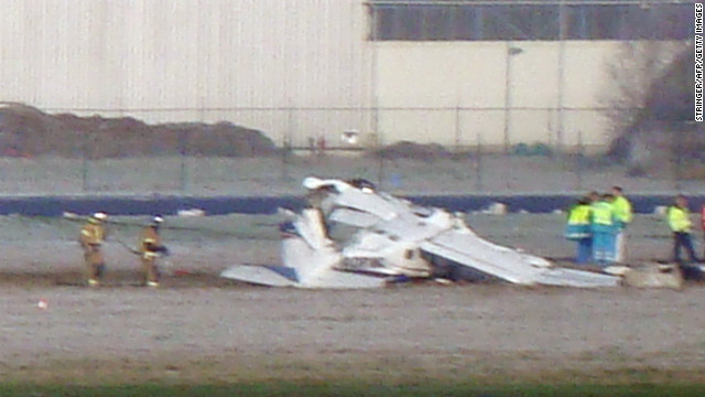 Rescuers gather around the crashed Cessna passenger plane at Brussels South airport in Charleroi, on February 9.