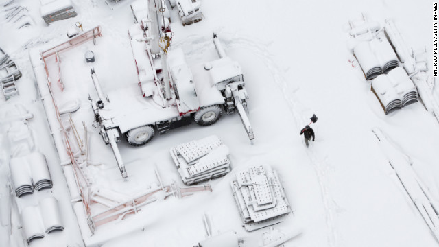 A worker carries a snow shovel across the Ground Zero construction sight on Saturday in New York.