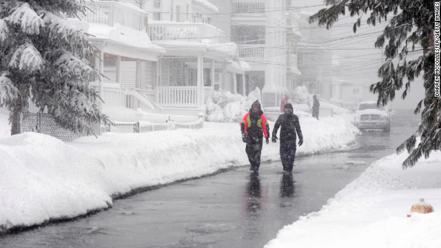 People walk along a street devoid of snow due to ocean flooding Saturday in Winthrop, Massachusetts. Coastal flooding is expected as the storm lingers into the day.