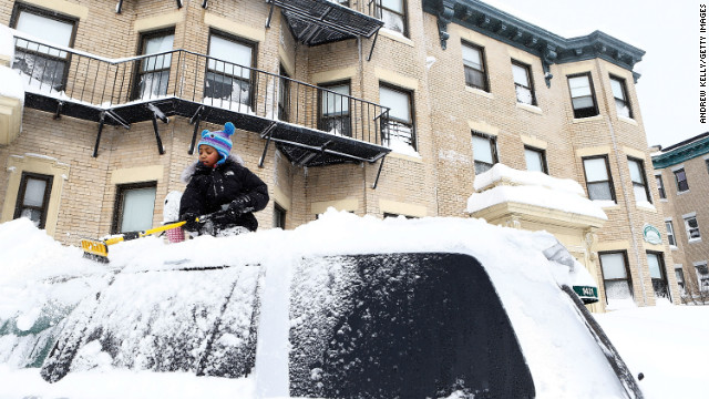 Saniyyah Phillips, 8, scrapes the snow off of the top of her father's car in the Brighton neighborhood of Boston on Friday.