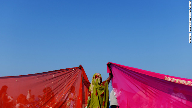 An Indian woman holds up the corners of two saris to dry on the banks of the Sangam on February 10.