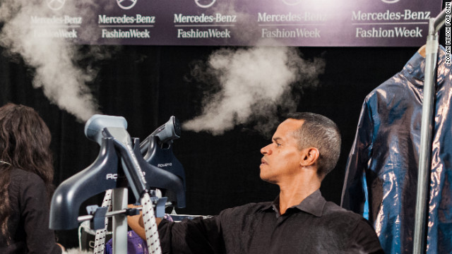Tailors use steam machines to remove wrinkles from outfits backstage at the Custo Barcelona show on February 10.