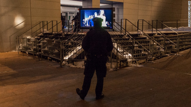 A New York police officer watches fashion show replays late Saturday, February 9, while guarding the Lincoln Center.