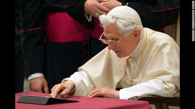 Pope Benedict XVI clicks on a tablet to send his first twitter message at the Paul VI hall at the Vatican, December 12, 2012.