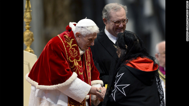 Benedict, accompanied by Grand Master Matthew Festing of the Sovereign Military Order of Malta, right, shakes hands with a woman after the Mass in St. Peter's Basilica to mark the 900th anniversary of the Order of the Knights of Malta on February 9, 2013, at the Vatican.
