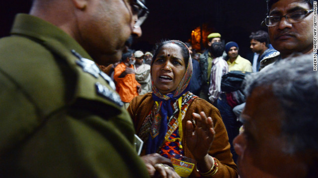 The relative of a traveler that was killed during a stampede at the railway station in Allahabad, talks to policemen on February 10, 2013.