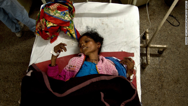 A woman lies on a bed after being injured in a stampede at the main railway station serving India's giant Kumbh Mela festival.
