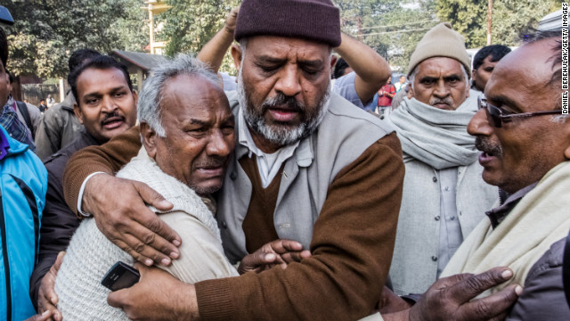 Men grieve on February 11, after a railroad station crush that left 36 people dead Sunday at the Kumbh Mela festival in Allahabad, India. 
