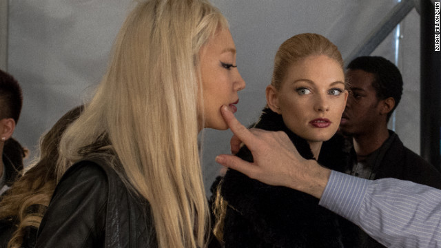 A model gets a touchup backstage at the Dennis Basso show on February 12.