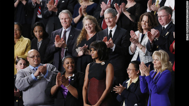 First lady Michelle Obama, center, is recognized by the audience and special guests surrounding her before President Barack Obama's 2013 State of the Union speech. Front row, left to right: Marine Sgt. Sheena Adams, Nathaniel and Cleopatra Pendelton, Michelle Obama, Menchu de Luna Sanchez and Jill Biden. Second row, left to right: Oregon Gov. John Kitzhaber, Deb Carey, Apple CEO Tim Cook, Amanda McMillan and Oak Creek Police Lt. Brian Murphy.