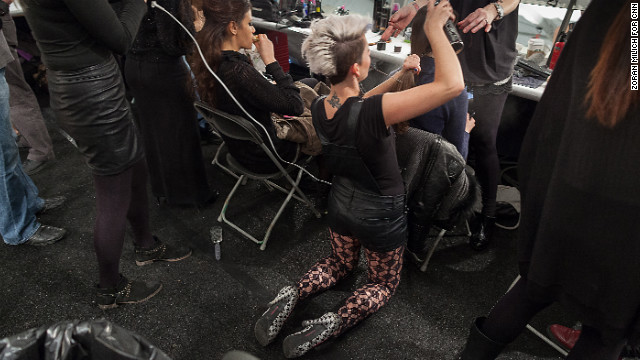 Stylist Lindsay Mikasell works with the hair and makeup crew at the Falguni and Shane Peacock show on February 13.