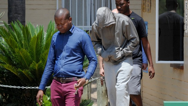 Pistorius leaves the Boshkop police station with his face covered on February 14, 2013.