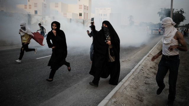 Bahraini protesters run for cover from tear gas following an anti-government rally to demand political reforms on Tuesday