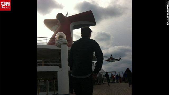 Passengers aboard the disabled Carnival Triumph cruise ship wave to a helicopter overhead as it approaches the vessel on February 14.