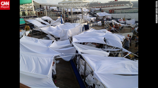 iReporter Robin Goebel says passengers dubbed an area &quot;tent city&quot; where many had chosen to set up temporary shelters on the deck of the disabled Carnival Triumph. Many slept on the decks of the ship because the rooms were too hot. 