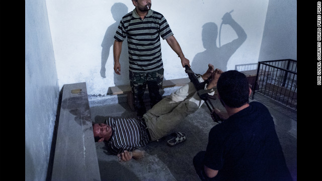<strong>Second prize -- spot news single: </strong><!-- --> </br>Syrian opposition fighters interrogate captured government informants on July 31, 2012, in Aleppo, Syria, in a photograph by Emin Ozmen. The informants were declared guilty and tortured throughout the night, according to Ozmen.