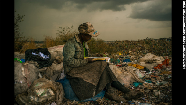 <strong>First prize -- contemporary issues single: </strong>A woman stops to read a book during her shift picking up trash at a dump near slums in Nairobi, Kenya, on April 3, 2012.