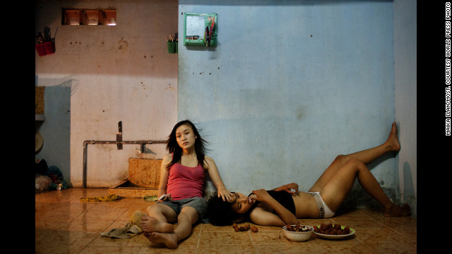 <strong>First prize -- contemporary issues stories: </strong><!-- --> </br>Phan Thi Thuy Vy and Dang Thi Bich Bay watch TV after studying on June 22, 2012, in Da Nang, Vietnam. The couple have been together for a year, according to photographer Maika Elan, in a country that's been hostile to same-sex relationships in the past.