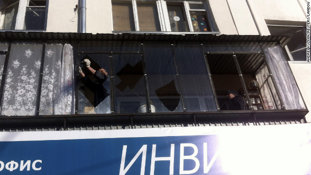 A man removes shards of glass from the frame of a broken window. 