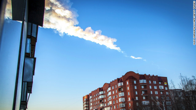 The trail of a falling object is seen above a residential apartment block in the Urals city of Chelyabinsk, on February 15, 2013. A heavy meteor shower rained down today on central Russia, sowing panic as the hurtling space debris smashed windows and injured dozens of stunned locals, officials said.