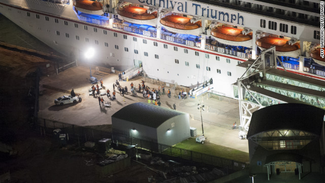 Members of the media wait for the last passengers to disembark the ship.