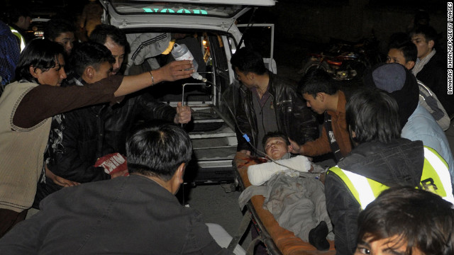 Relatives and medical staff shift an injured bomb blast victim into an emergency vehicle. 