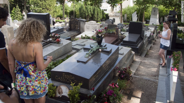 And still they come. Visitors pay respects at the grave of legendary French singer dith Piaf at Pre Lachaise Cemetery in Paris.