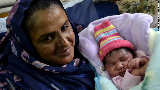 Mukhtar Mai smiles next to her new born baby boy at a hospital in Multan on December 5, 2011.