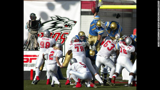 University of New Mexico kicker Katie Hnida, No. 2, attempts an extra point against UCLA in the Las Vegas Bowl on December 25, 2002, becoming the first woman to play in a Division I-A football game. The kick was blocked, but she later became the first woman to score points in college football's top division. 