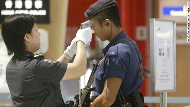 Airport police have their temperature checked before entering the restricted area at Hong Kong International Airport, September 9, 2003. 