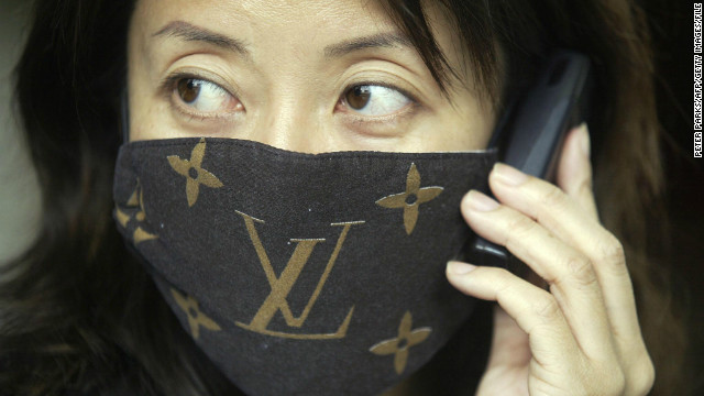 A woman wears a mask with &quot;Louis Vuitton&quot; branding to protect against SARS, April 3, 2003.