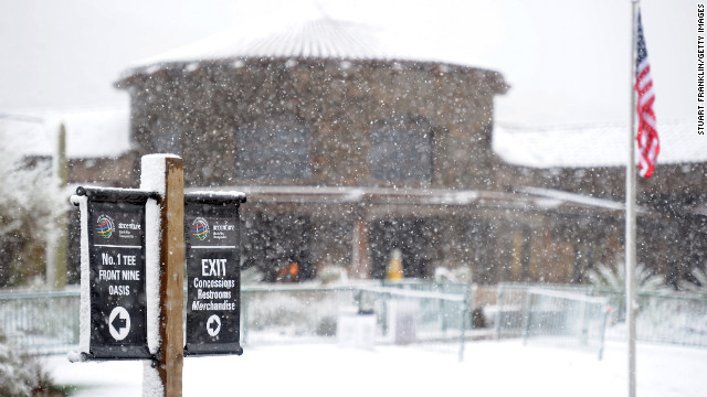 Snow covers the clubhouse behind the 18th green during the first round of the tournament at Dove Mountain on Wednesday.
