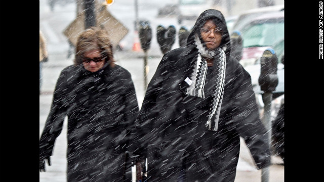 Pedestrians make their way to work through the snow in downtown Wichita, Kansas, on Wednesday, February 20.