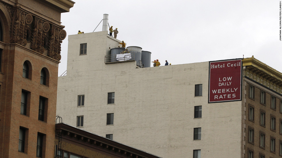 Firefighters work to remove a body found inside a water tank on the rooftop of the Cecil Hotel in Los Angeles on Tuesday, February 19. A young woman's body had likely been decomposing for more than two weeks, police said.