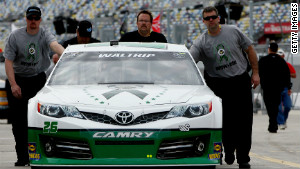 Crew members push the No. 26 through a garage area during practice for Sunday\'s Daytona 500.
