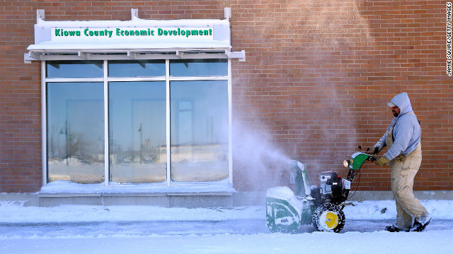 A worker uses a snowblower to clear a path on February 22 in Greensburg, Kansas.