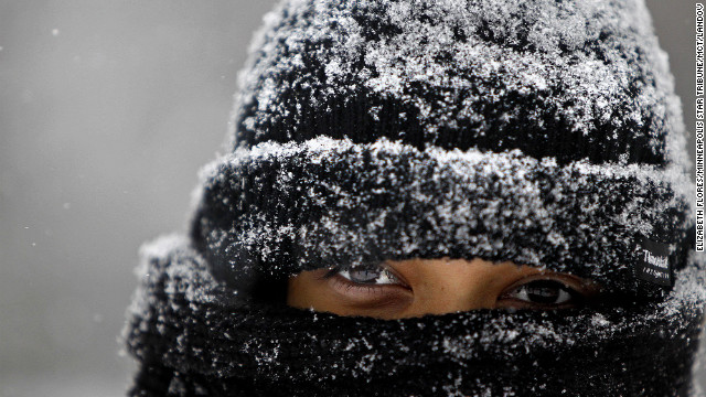 Jackie Arrandondo, 19, is covered with morning snow from head to toe as she waits for a city bus Friday, in Minneapolis. Gusty winds and iced-over roadways made for treacherous Midwest travel Friday as a major winter storm headed east over the Great Lakes. Two deaths have been linked to the storm, including one in a fatal traffic accident in Minnesota.
