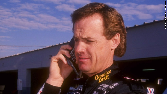 NASCAR driver Rusty Wallace talks on a cellphone during practice for the Daytona 500 in February 1996. Perhaps he's complaining to his barber about his hair.