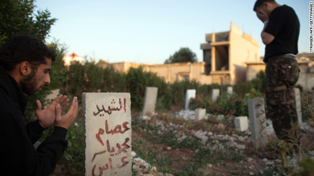 Members of the Free Syrian Army's Mugaweer (commandos) Brigade pay their respects in a cemetery on May 12, 20<br /> 7000<br /> 12 in Qusayr.