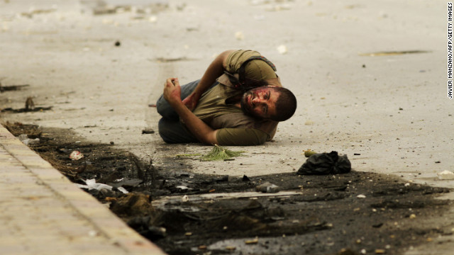 A man lies on the ground after being shot by a sniper for a second time as he waits to be rescued by members of the Al-Baraa Bin Malek Battalion, part of the Free Syria Army's Al-Fatah brigade, in Aleppo on October 20.