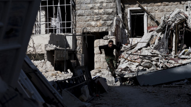 A Syrian rebel leaps over debris left in the street while running across a
