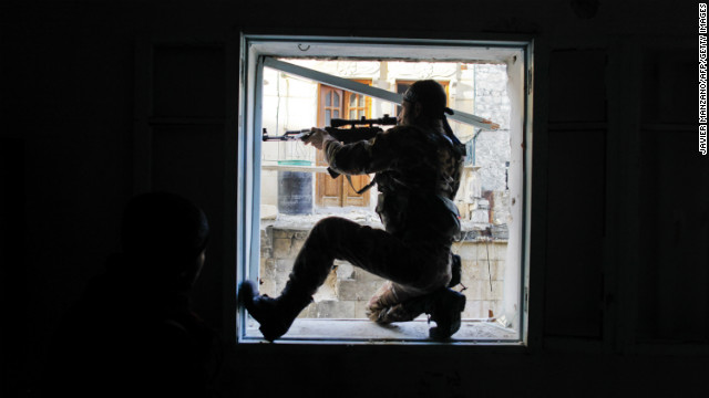 A member of Liwa Salahadin aims at a regime fighter in the besieged district of Karmel al-Jabl in Aleppo on December 6.