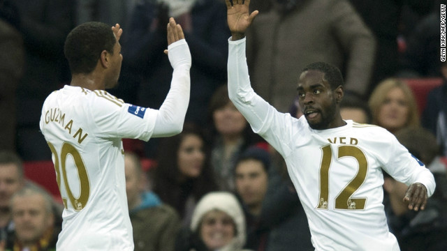 Swansea scorers Jonathan de Guzman and Nathan Dyer celebrate on their way to a 5-0 League Cup final win over Bradford at Wembley. 